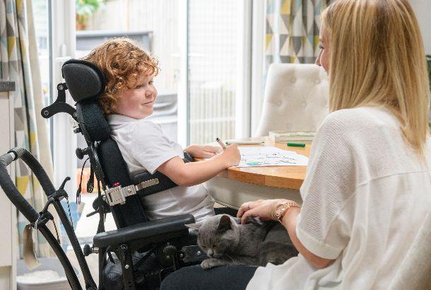 moeder met zoon in rolstoel zitten thuis aan tafel